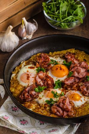 papas doradas: American Hash Browns potato with fried egg, bacon and herbs, real american breakfast Foto de archivo