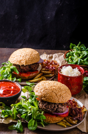 hot sauce: Beef burger with bacon and home french fries, little salad and hot sauce. Stock Photo