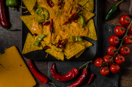 nacho chip: Baked Nachos with cheese dip and chili peppers