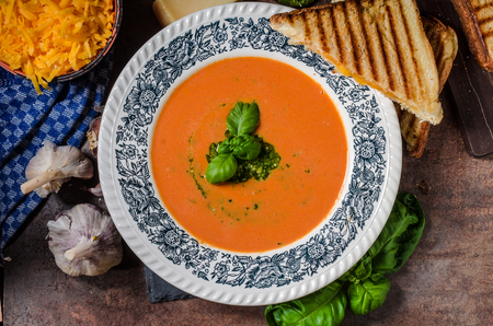 cheddar cheese: Roasted tomato soup with French toast and cheddar cheese, pesto inside soup Stock Photo