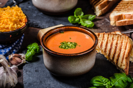 Roasted tomato soup with French toast and cheddar cheese, pesto inside soup Standard-Bild