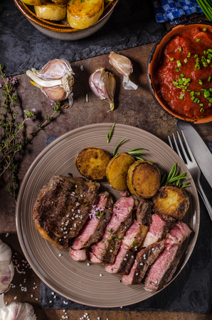 costilla: Rib eye steak with herbs, roasted potatoes, hot tomato garlic sauce and herbs