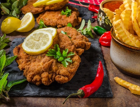 schnitzel: Schnitzel with fries, salad and herbs, hot chilli tomato sauce