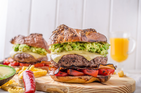 Beef burger with avocado dip and baked tomato Stock Photo