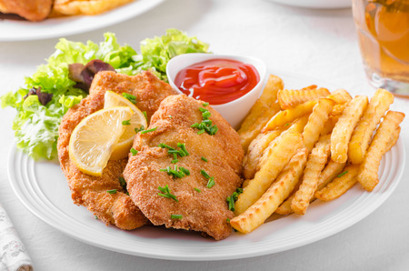 Wiener schnitzel with french fries, salad and a sharp dip Stock fotó