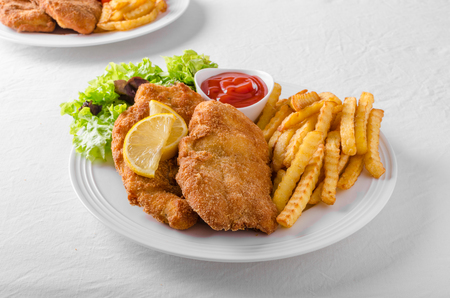 Wiener schnitzel with french fries, salad and a sharp dip Standard-Bild