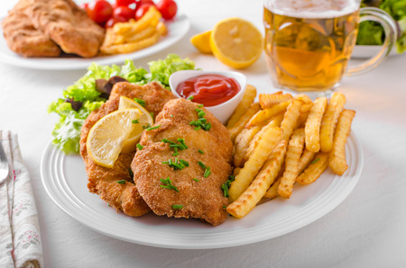 Wiener schnitzel with french fries, salad and a sharp dip Stock Photo