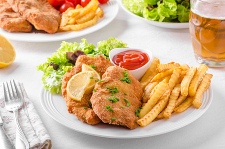 wiener: Wiener schnitzel with french fries, salad and a sharp dip Stock Photo