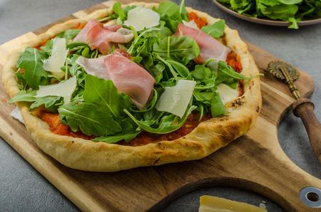 parma ham: Rustic pizza with arugula, Parma ham and Parmesan Stock Photo