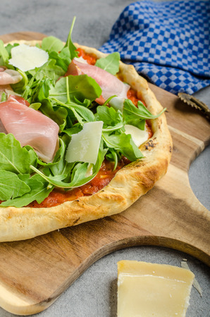 Rustic pizza with arugula, Parma ham and Parmesan Stock Photo