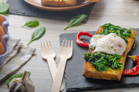 poached: Toasted baguette with poached egg and garlic spinach Stock Photo