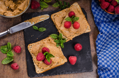 styled: Toast with peanut butter and berries, rustic composition, styled with mint, homemade peanut butter