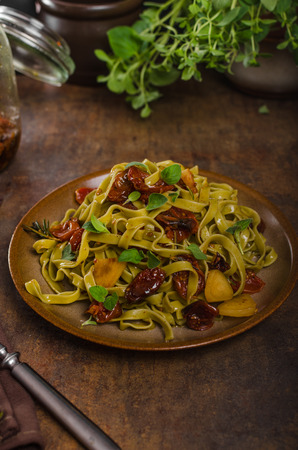 pasta with sun dried tomatoes and roasted garlic olive oil, fresh hebs in Stock Photo
