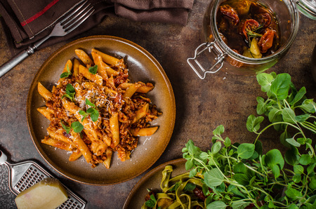 Pasta arrabiata delicious, spicy and simple delicious pasta with meat and parmesan cheese Standard-Bild