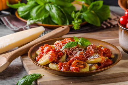 Roasted gnocchi with tomato souce, parmesan cheese and herbs Stock Photo