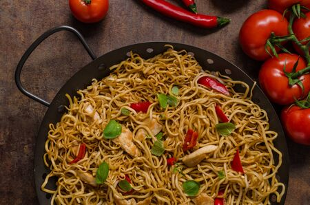 fry: Chinese noodles chicken, hot peppers and garlic in Stock Photo