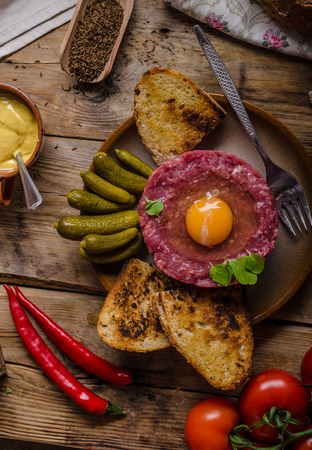 Beef tartare dish, delicious full protein dish with spices, mustard, egg and fried bread with garlic