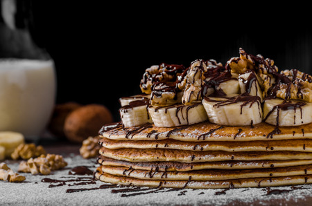 Rustic pancakes with banana and chocolate, roasted nuts on top
