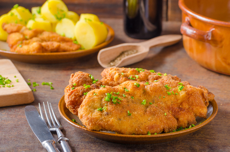 Original Weiner schnitzel with potatoes and herbs Standard-Bild