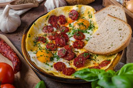 Omelette with chorizo and herbs, fresh bread, tasty bio herbs Stock Photo
