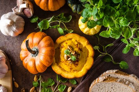 Creamy pumpkin soup with fresh bread, halloween soup