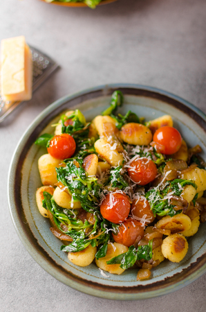 Gnocchi with spinach, garlic and tomatoes, styled photo for advertising Stock Photo