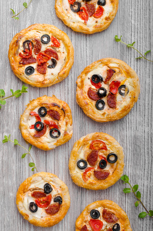 mini pizza: Puff pastry mini pizza with herbs, olives and sausages Stock Photo