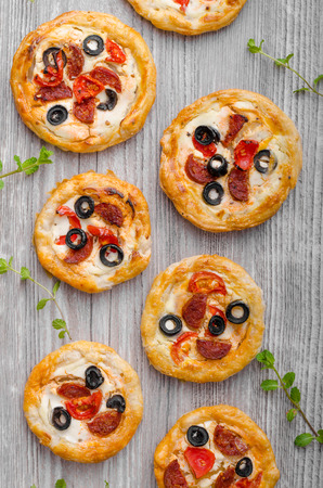 mini oven: Puff pastry mini pizza with herbs, olives and sausages Stock Photo