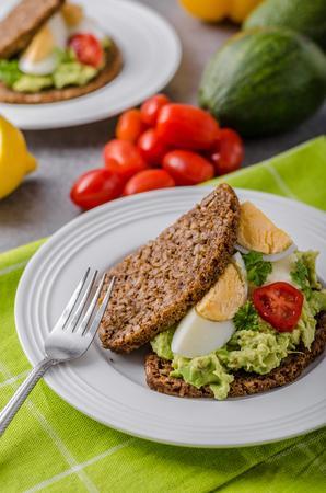Healthy bread with avocado spread, lemon, vegetable and eggs