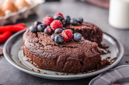 Brownies cake delish with berries, milk and eggs behind as background Stock Photo
