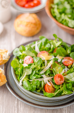 Lamb lettuce salad with dijon dressing, crispy bun and parmesan cheese on top Stock Photo