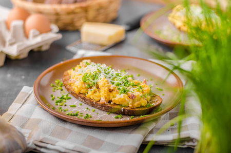Scrambled eggs with cheese and herbs, on panini bread Reklamní fotografie