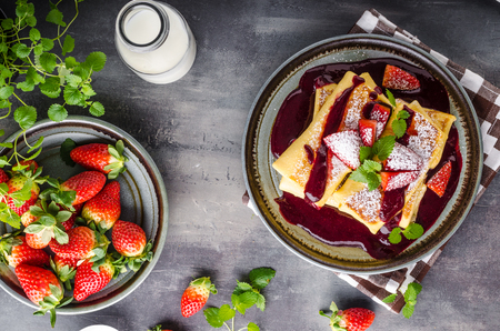 Filled pancakes with strawberries, fresh berries and sauce Фото со стока