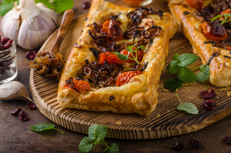 Puff pastry vegetarian pizza with caramelized onion, herbs garlic and tomatoes Stock Photo