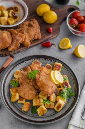 Schnitzel original with lemon and gnocchi fried, delish tasty food mini schnitzels
