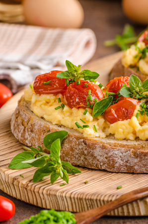 scrambled: Bread scrambledd eggs, delish breakfast with herbs and tomatoes Stock Photo