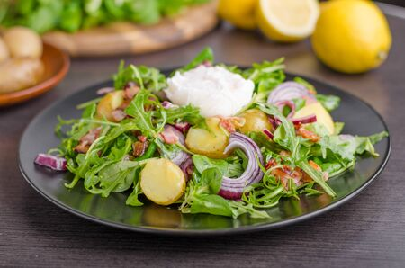 Potato lettuce salad with poached egg and onion