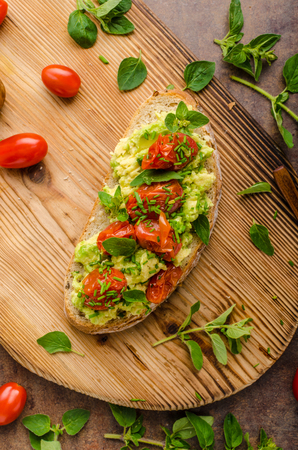 Avocado spread with tomatoes, roasted tomatoes and herbs on top