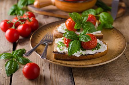Avocado spread bread with baked tomato salad, fresh basil Stock Photo
