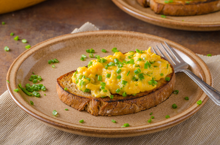 Scrambled eggs with herbs, simple, full protein breakfast with fresh herbs and fried english bread Stock Photo