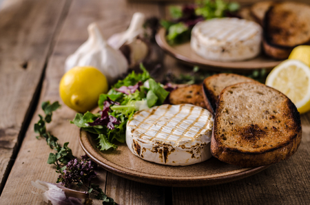 Grilled camembert cheese, mini salad and baked bread Stock fotó