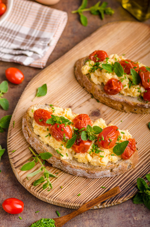 Bread scrambledd eggs, delish breakfast with herbs and tomatoes Stock Photo