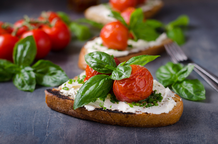 Bread cheese spread baked tomato, fresh basil on top Stok Fotoğraf