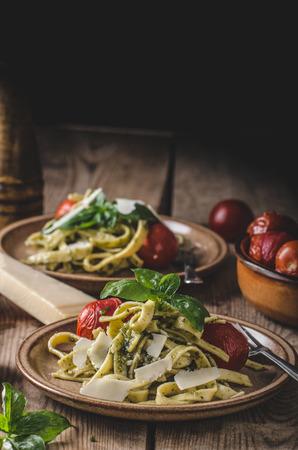 Pasta pesto basilicum, verse tomaten, geraspte Parmezaanse kaas