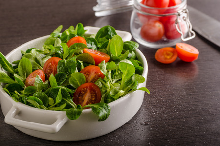 Lamb lettuce salad, tomatoes and herbs, food photography