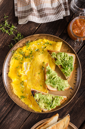 Egg omelette with garlic avocado toast, bio eggs and fresh herbs, homemade ketchup