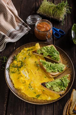 Egg omelette with garlic avocado toast, bio eggs and fresh herbs, homemade ketchup