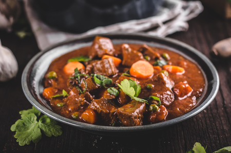 Beef stew with carrots, food photography, lot of herbs inside stew Stok Fotoğraf - 96849475