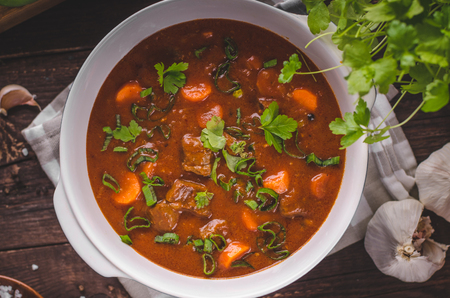 Beef stew with carrots, food photography, lot of herbs inside stew Stock fotó - 96849477