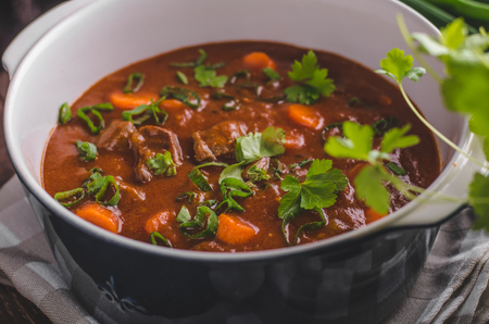 Beef stew with carrots, food photography, lot of herbs inside stew Stockfoto - 96849522